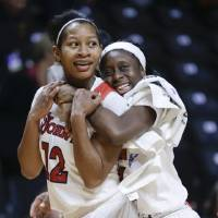 Photo - St. John's guard Briana Brown (12) is hugged by Aaliyah Lewis, right, as they leave the court after St. John's defeated Southern California 71-68 in an NCAA women's college basketball first-round tournament game Saturday, March 22, 2014, in Knoxville, Tenn. Brown hit a 3-point shot to give St. John's the win. (AP Photo/Mark Humphrey)