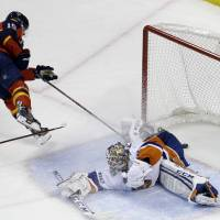 Photo - Florida Panthers' Scottie Upshall (19) scores a goal against New York Islanders goalie Kevin Poulin during the second period of an NHL hockey game, Tuesday, Jan. 14, 2014, in Sunrise, Fla. (AP Photo/Lynne Sladky)