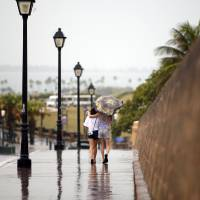 Photo - Two women walk with the protection of an umbrella in Old San Juan, Puerto Rico, Saturday, Aug. 2, 2014. Bertha pushed just south of Puerto Rico on Saturday as it unleashed heavy rains and strong winds across the region. (AP Photo/Ricardo Arduengo)