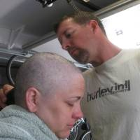 Photo - In this August 2012 photo provided by Arrica Wallace, husband Matthew shaves Arrica's head when her hair was falling out in Manhattan, Kan. Arrica Wallace was 35 when her cervical cancer was discovered in 2011. It spread widely, with one tumor so large that it blocked half of her windpipe. The strongest chemotherapy and radiation failed to help, and doctors gave her less than a year to live. But her doctor heard about an immune therapy trial at the Cancer Institute and got her enrolled.