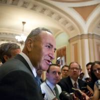 Photo - Sen. Chuck Schumer, D-N.Y., chairman of the Senate Rules Committee, speaks with reporters just off the Senate floor as lawmakers moved toward resolving their feud over Republican filibusters of White House appointees, at the Capitol in Washington, Tuesday, July 16, 2013. The Senate just voted 71-29 to end a two-year Republican blockade that was preventing Richard Cordray from winning confirmation as director of the Consumer Financial Protection Bureau.  (AP Photo/J. Scott Applewhite)