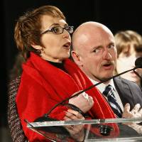 Photo - FILE - Rep. Gabrielle Giffords, left, leads the Pledge of Allegiance accompanied by her husband, former astronaut Mark Kelly, at the start of a one year memorial vigil for the victims and survivors of the shooting that wounded Giffords, 12 others and killed six in this Sunday, Jan. 8, 2012 file photo taken in Tucson, Ariz. The three-year anniversary of the shooting of Gabrielle Giffords will be marked Wednesday Jan. 8, 2013 with bell-ringing, flag-raising and other ceremonies, providing a moment of reflection for the former congresswoman. Giffords and Kelly plan to mark the anniversary privately with friends and other survivors of the attack. (AP Photo/Matt York, File)