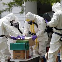 Photo - Federal agents wearing hazardous material suits and breathing apparatus inspect the home and possessions in the West Hills Subdivision house of Paul Kevin Curtis in Corinth, Miss., Friday, April 19, 2013. Curtis is in custody under the suspicion of sending letters covered in ricin to the U.S. President Barack Obama and U.S. Sen. Roger Wicker, R-Miss. (AP Photo/Rogelio V. Solis)