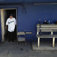Photo - Pete Rose walks out of the dugout at The Ballpark at Harbor Yard, Monday, June 16, 2014, in Bridgeport, Conn. Rose, banned from Major League Baseball, returned to the dugout for one day to manage the independent minor-league Bridgeport Bluefish. (AP Photo/Jessica Hill)
