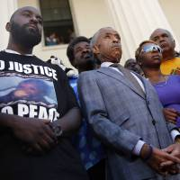Photo - Civil rights leader Rev. Al Sharpton, center, stands with the parents of Michael Brown, Lesley McSpadden, right, and Michael Brown Sr., left, during a news conference outside the Old Courthouse Tuesday, Aug. 12, 2014, in St. Louis. Brown Jr., 18, who was unarmed, was shot to death Saturday by a Ferguson police officer while walking with a friend down the center of the street. (AP Photo/Jeff Roberson)