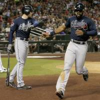 Photo - Atlanta Braves' Jason Heyward, right, slaps hands with teammate Freddie Freeman, middle, after Heyward scored a run as Arizona Diamondbacks pitcher Brandon McCarthy, left, walks behind home plate during the seventh inning of a baseball game on Friday, June 6, 2014, in Phoenix. (AP Photo/Ross D. Franklin)