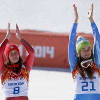 Photo - Women's downhill gold medalists Switzerland's Dominique Gisin, left, and Slovenia's Tina Maze, right, applaud during a flower ceremony at the Sochi 2014 Winter Olympics, Wednesday, Feb. 12, 2014, in Krasnaya Polyana, Russia. (AP Photo/Gero Breloer)