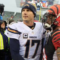 Photo - San Diego Chargers quarterback Philip Rivers (17) shakes hands with Cincinnati Bengals linebacker Rey Maualuga after a 27-10 win over the Bengals in an NFL wild-card playoff football game on Sunday, Jan. 5, 2014, in Cincinnati. (AP Photo/Tom Uhlman)