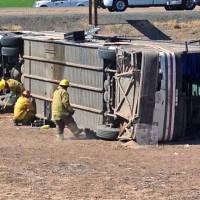 Photo - Emergency personnel respond to the scene of a fatal accident in Blythe, Calif. on Wednesday, May 21, 2014. A tractor-trailer spilled a load of steel pipes onto a highway, triggering a bus crash Wednesday that killed four people and seriously injured several others on the main road linking Southern California and Arizona, authorities said. (AP Photo/Brian Skoloff)
