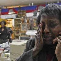 Photo - Edeline B. Clermont weeps in the