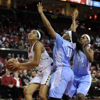 Photo - Maryland's Tianna Hawkins , left, looks to shoot as North Carolina's Brittany Roundtree, center, defends during the first half of an NCAA college basketball game on Thursday, Jan. 24, 2013, in College Park, Md. North Carolina's Xylina McDaniel, right, watches the play. (AP Photo/Gail Burton).
