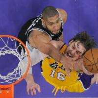 Photo - Los Angeles Lakers forward Pau Gasol, right, of Spain, and San Antonio Spurs forward Tim Duncan battle for a rebound during the second half in Game 3 of a first-round NBA basketball playoff series, Friday, April 26, 2013, in Los Angeles. The Spurs won 120-89. (AP Photo/Mark J. Terrill)
