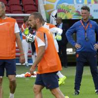 Photo - Netherlands' head coach Louis van Gaal, right, looks at the players Arjen Robben, left, and Wesley Sneijder, center, during the official training the day before the group B World Cup soccer match between Australia and the Netherlands at the Estadio Beira-Rio in Porto Alegre, Brazil, Tuesday, June 17, 2014.  (AP Photo/Michael Sohn)