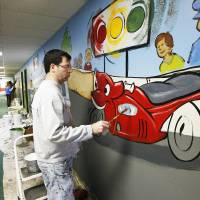 Photo - Joel Randell with Palmer Studios works on a mural at Oakcrest Church of Christ.