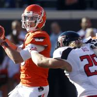 Photo -   Oklahoma State quarterback Clint Chelf, left, passes under pressure from Texas Tech linebacker Blake Dees (25) as Oklahoma State offensive lineman Brandon Webb (51) blocks in the first quarter of an NCAA college football game in Stillwater, Okla., Saturday, Nov. 17, 2012. (AP Photo/Sue Ogrocki)