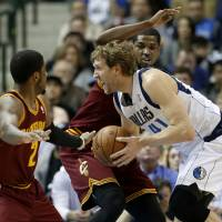 Photo - Dallas Mavericks power forward Dirk Nowitzki (41) of Germany drives between Cleveland Cavaliers' Kyrie Irving (2) and Tristan Thompson, rear, to the basket for a shot attempt in the first half of an NBA basketball game, Monday, Feb. 3, 2014, in Dallas. (AP Photo/Tony Gutierrez)