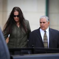 Photo - Former 404th state District Judge Abel Limas, right, quickly exits the federal courthouse in Brownsville, Texas on Wednesday, Aug. 21, 2013. Limas, who turned his courtroom into a money-making operation, was sentenced Wednesday to six years in prison followed by three years of unsupervised release on one count of racketeering in Brownsville.  (AP Photo/The Brownsville Herald, Yvette Vela)