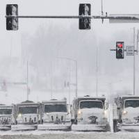 Photo - Snow plows stop for a traffic signal as they clear several lanes of West 6th Street in Lawrence, Kan., Sunday, March 24, 2013. Few signs of spring are being found in parts of the Midwest as a snowstorm brings heavy snow and high winds. (AP Photo/Orlin Wagner)