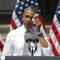 Photo - FILE - This June 25, 2013 file photo shows President Barack Obama wiping perspiration from his face as he speaks about climate change at Georgetown University in Washington. The Obama administration is poised to unveil first-ever rules limiting greenhouse gas emissions from the power plants that dot the U.S. map. President Barack Obama says the rules are essential to curb climate change, but critics disagree.  (AP Photo/Charles Dharapak, File)