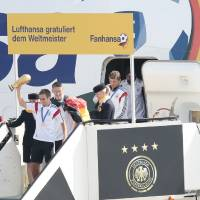 """Photo - The players of German national soccer team, Philipp Lahm with trophy , Sebastian Schweinsteiger, Thomas Mueller and Sami Khedira, from left arrive at Tegel  airport in Berlin Tuesday, July 15, 2014.  Germany's World Cup-winning team has returned home from Brazil to celebrate the country's fourth title with huge crowds of fans. The team's Boeing 747 touched down at Berlin's Tegel airport midmorning Tuesday after flying a lap of honor over the """"fan mile"""" in front of the landmark Brandenburg Gate.  Words read Lufthansa congratulates the World Champion, Fanhansa.  (AP Photo/Markus Schreiber)"""