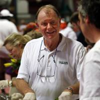 Photo - Joe Sparks with Legends Restaurant serves salad during Taste of Norman on Thursday. PHOTO BY STEVE SISNEY, THE OKLAHOMAN  STEVE SISNEY