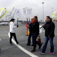 Photo - Clerical workers carry signs in protest at the Port of Long Beach, Calif. on Tuesday, December 4, 2012. Los Angeles Mayor Antonio Villaraigosa says both sides in a strike at the twin ports of Los Angeles and Long Beach have agreed to federal mediation. However, the union representing clerical workers says the strike now in its eighth day will continue. Clerical workers are striking 10 terminals at the nation's busiest port complex and dockworkers won't cross picket lines. (AP Photo/Nick Ut)
