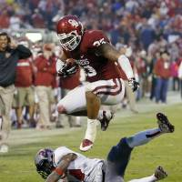 Photo -  Oklahoma fullback Trey Millard (33) jumps over Texas Tech defensive back Bruce Jones (24) in the fourth quarter of an NCAA college football game in Norman, Okla., Saturday, Oct. 26, 2013. Oklahoma won 38-30. (AP Photo/Sue Ogrocki)