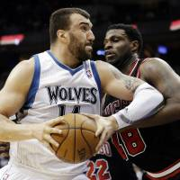 Photo - FILE - In this March 24, 2013, file photo, Minnesota Timberwolves' Nikola Pekovic, left, of Montenegro, drives against Chicago Bulls' Nazr Mohammed during an NBA basketball game in Minneapolis. After weeks of negotiations, waiting and watching, Pekovic and the Timberwolves came to agreement on Wednesday, Aug. 14, 2013, on a new five-year contract worth $60 million that includes an additional $8 million in incentives. (AP Photo/Jim Mone, File)