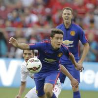Photo - Manchester United's Angelo Henriquez, front, moves the ball as Inter Milan's Ruben Botta, center, defends during the first half of a soccer game at  the 2014 Guinness International Champions Cup, Tuesday, July 29, 2014, in Landover, Md. (AP Photo/Luis M. Alvarez)