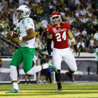 Photo - Oregon quarterback Marcus Mariota (8) runs into the end zone for a touchdown during the second quarter of an NCAA college football game against South Dakota in Eugene, Ore., Saturday, Aug. 30, 2014. (AP Photo/Ryan Kang)