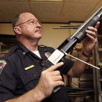 Photo - Choctaw Police Chief Conny Clay shows off one of several shotguns gathering dust in the department's property room on Thursday, July 26, 2012.  Photo by Jim Beckel, The Oklahoman.  Jim Beckel - THE OKLAHOMAN