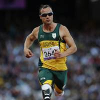Photo - FILE - In this Sept. 5, 2012 file photo, South Africa's Oscar Pistorius competes during Men's 100m T44 round 1 at the 2012 Paralympics in London. A judge in South Africa says Pistorius, who is charged with murdering his girlfriend, can leave South Africa to compete in international competition, with conditions. (AP Photo/Emilio Morenatti, File)