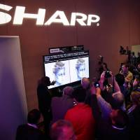 Photo - Journalists check out the new Sharp 4K lite television during a news conference at the Consumer Electronics Show press day on Monday, Jan. 6, 2014, in Las Vegas. (AP Photo/Isaac Brekken)