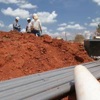 Photo -  Workers lay pipe for the city's first splash pad, at Barnett Fields at Main Street and Kelly Avenue. The pad is expected to be finished by the end of August. PHOTO BY PAUL HELLSTERN, THE OKLAHOMAN.   PAUL HELLSTERN