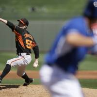 Photo - San Francisco Giants' Tim Lincecum pitches to the Kansas City Royals in the second inning of a spring training baseball game, Friday, March 7, 2014, in Surprise, Ariz. (AP Photo/Tony Gutierrez)