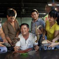 Photo - Chef Khai Duong is surrounded by employees of Quan Oc Thanh Hien seafood restaurant in Nha Trang, Vietnam. (LiPo Ching/San Jose Mercury News/MCT)