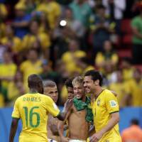 Photo - Brazil's Neymar, center, chats with his teammates Fred, right, and Ramires after  a 4-1 win over Cameroon during the group A World Cup soccer match between Cameroon and Brazil at the Estadio Nacional in Brasilia, Brazil, Monday, June 23, 2014. (AP Photo/Dolores Ochoa)