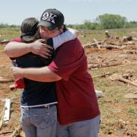 Photo - Andrea Rush, left, gets a hug from Timothy Walser at the Hide-A-Way Mobile Home Park in Woodward, Okla., Monday, April 16, 2012. Rush's friend Steve Peil was killed by a tornado that struck the town early Sunday morning. Members of Walser's family knew Peil. Walser was at the site helping to clean up the debris from destroyed homes, including one in which his cousins lived. Photo by Nate Billings, The Oklahoman