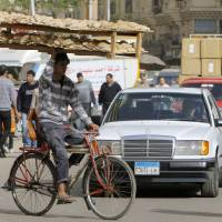 Photo - An Egyptian bread vendor rides his bicycle in downtown Cairo, Egypt, Saturday, March 16, 2013. Owners of state-subsidized bakeries protested Saturday against changes to the distribution system of subsidized wheat. It comes amid economic reforms the government is seeking to implement to boost the economy and ensure subsidized bread reaches millions of poor Egyptians who complain that the bakeries sell the wheat for a profit. (AP Photo/Amr Nabil)