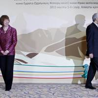 Photo - EU foreign policy chief Catherine Ashton, left, smiles, as Secretary of Iran's Supreme National Security Council Saeed Jalili walks away, after a photo call at a start of high-level talks between world powers and Iranian officials in Almaty, Kazakhstan on Friday, April 5, 2013. (AP Photo/Shamil Zhumatov, Pool)