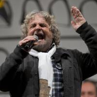 Photo - Italian comic-turned-political agitator Beppe Grillo, leader of the anti-establishment 5 Star Movement, delivers his speech during a final rally in view of the upcoming general elections, in Rome, Friday, Feb. 22, 2013. Grillo fills piazzas from Palermo deep in the south to Verona up north with Italians who seem to get some catharsis from his rants against the politicians who drove the country to the brink of financial ruin, the captains of industry whose alleged illegal shenanigans are tarnishing prized companies, and the bankers who aided and abetted both. (AP Photo/Andrew Medichini)