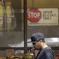 Photo - In this July 7, 2014 photo, a man drinks out of a coffee cup as he walks under a sign opposed to taxes on sugary drinks posted in the window of Casa Thai Market in San Francisco. San Francisco and Berkeley are aiming to become the first U.S. cities to pass per-ounce taxes on sugary drinks. (AP Photo/Jeff Chiu)