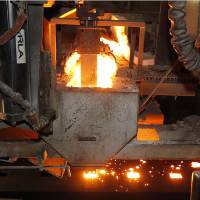 Photo - In this May 12, 2014 photo, molten metal is cast at Rochester Metal Products Corp. in Rochester, Ind. The hulking induction furnaces the plant uses to melt scrap iron consume enough electricity to power 7,000 households. (AP Photo/AJ Mast)