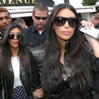 Photo - Kim Kardashian, front and Kourtney Kardashian, left, leave at a restaurant in Paris, Thursday, May 22, 2014. The gates of the Chateau de Versailles, once the digs of Louis XIV, will be thrown open to Kim Kardashian, Kanye West and their guests for a private evening this week ahead of their marriage (AP Photo/Jacques Brinon)