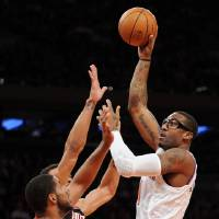 Photo - New York Knicks' Amare Stoudemire, right, shoots over Portland Trail Blazers' LaMarcus Aldridge and Jared Jeffries, rear, during the first quarter of an NBA basketball game, Tuesday, Jan. 1, 2013, at Madison Square Garden in New York. (AP Photo/Bill Kostroun)