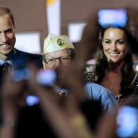 Photo - FILE - In this July 10, 2011, file photo, Prince William and wife Kate, the Duke and Duchess of Cambridge, are photographed by fans during a visit to the U.S. in Culver City, Calif. The palace announced Monday, Dec. 3, 2012, that Prince William and wife Kate are expecting their first child_ and it seems at times that Americans may be more enthralled by the news than the Brits. There are several reasons for the American public's pleasure in Kate's news, manifested not only by the good wishes sent by President Obama but also by the breathless news coverage and the general good will toward the couple. (AP Photo/Chris Pizzello, File)