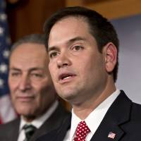 Photo - FILE - In this Jan. 28, 2013, photo, Sen. Marco Rubio, R-Fla., right, and Sen. Charles Schumer, D-N.Y., left, join a bipartisan group of leading senators to announce that they have reached agreement on the principles of sweeping legislation to rewrite the nation's immigration laws, during a news conference at the Capitol in Washington. Republicans face a delicate balancing act as they embrace immigration reform _ and no one is more symbolic of the potential risks and rewards than Rubio.  (AP Photo/J. Scott Applewhite)