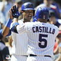 Photo - Chicago Cubs' Welington Castillo (5), celebrates with teammate Starlin Castro back, after hitting a two-run home run during the fourth inning of a baseball game against the Milwaukee Brewers in Chicago, Monday, Sept. 1, 2014. (AP Photo/Paul Beaty)