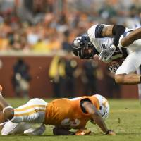 Photo - Tennessee defensive back Brian Randolph,  bottom, upends Utah State wide receiver Brandon Swindall (11) during the first half of their NCAA college football game at Neyland Stadium, Sunday, Aug. 31, 2014 in Knoxville, Tenn.  (AP Photo/Knoxville News Sentinel, Saul Young)