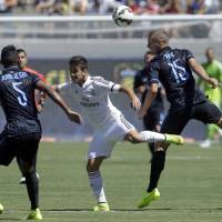 Photo - Inter Milan's Nemanja Vidic, right, and Real Madrid's Alvaro Medran, center, jump for the ball during the first half of a soccer match in the first round of the Guinness International Champions Cup, Saturday, July 26, 2014, in Berkeley, Calif. At left is Inter Milan's Juan Jesus. (AP Photo/Ben Margot)